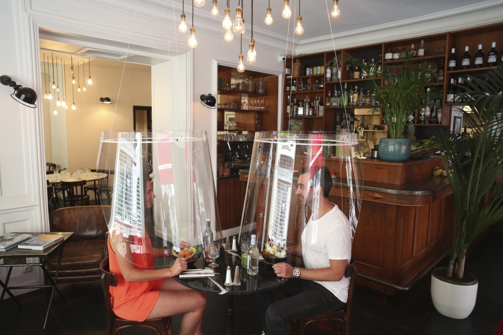 A man and a woman demonstrate dining under a plastic shield Wednesday, May 27, 2020 in a restaurant of Paris. As restaurants in food-loving France pre...