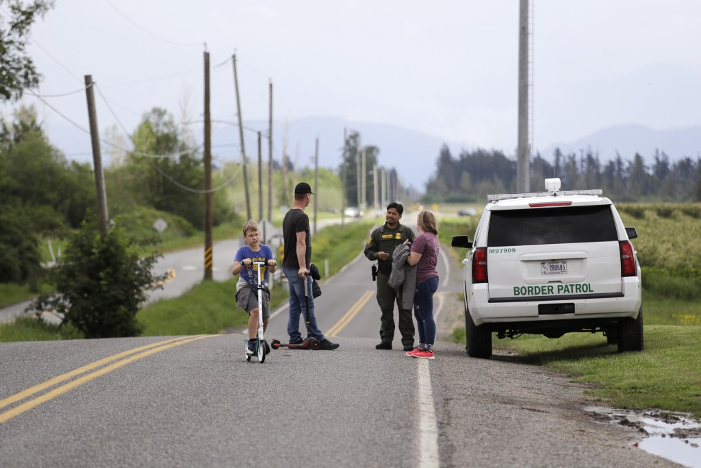 In this photo taken May 17, 2020, a Border Patrol officer in the U.S. talks with nearby residents on E. Boundary Rd., paralleling 0 Ave. behind them i...
