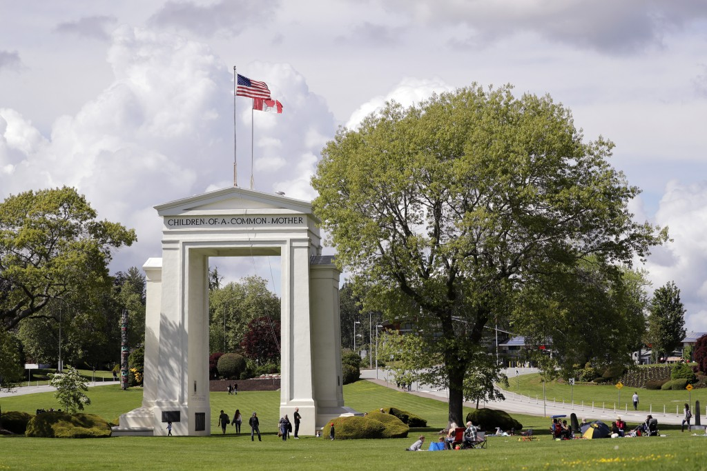 In this photo taken May 17, 2020, people walk back and forth across the border between the U.S. and Canada in Peace Arch Park in Blaine, Wash. With th...