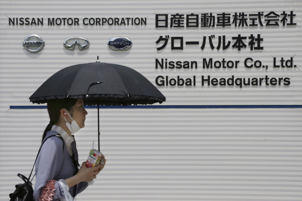 A woman walks past the global headquarters of Nissan Motor Co., Ltd. in Yokohama near Tokyo, Wednesday, May 27, 2020. The Japanese-French auto allianc...