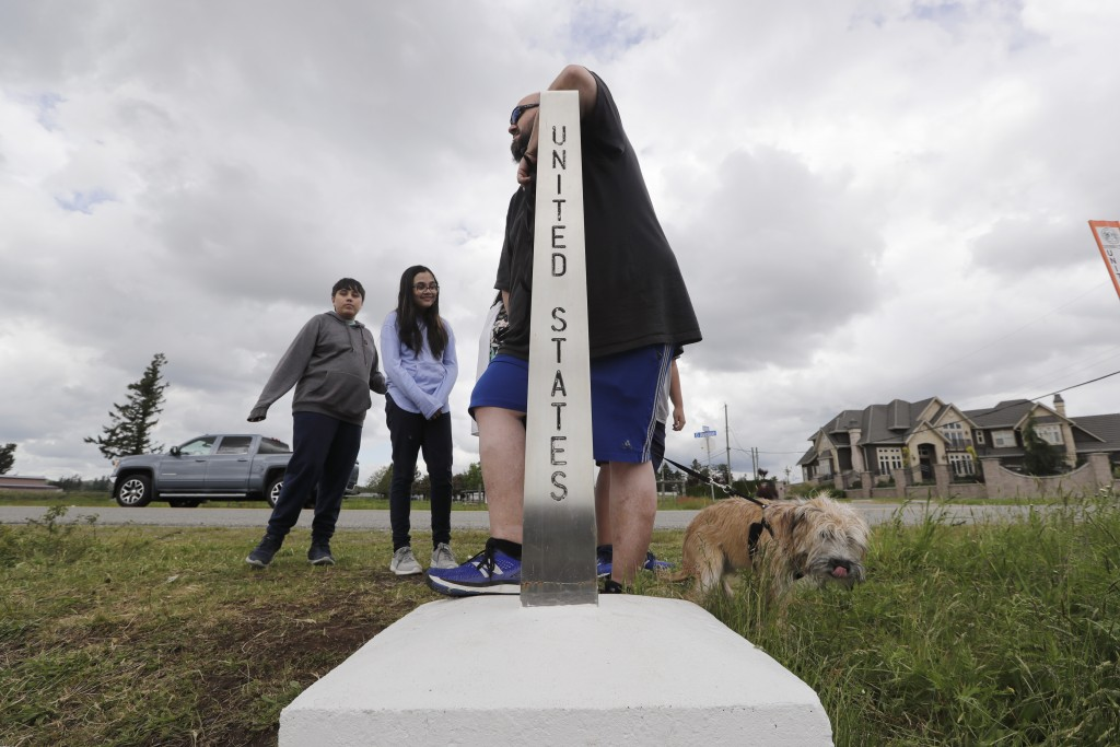 In this photo taken May 17, 2020, Darious Kilgore leans on a marker designating the border with the U.S. as he stands in Canada and visits with family...