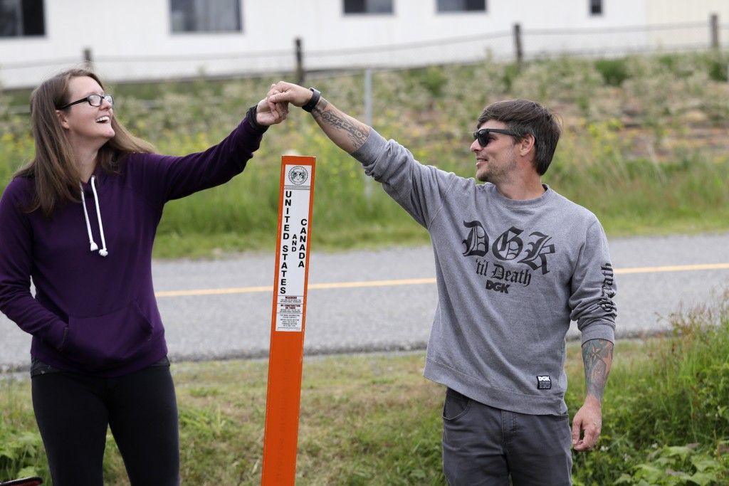 In this photo taken May 17, 2020, Kris Browning, left, stands in Canada and holds hands with her husband, Tim Browning, in the U.S., after posing for ...