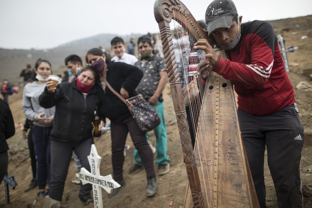 Harpist and cemetery worker Charlie Juarez performs while Gregoria Zumaeta, 44, left, mourns the death of her brothers Jorge Zumaeta, 50, and Miguel Z...
