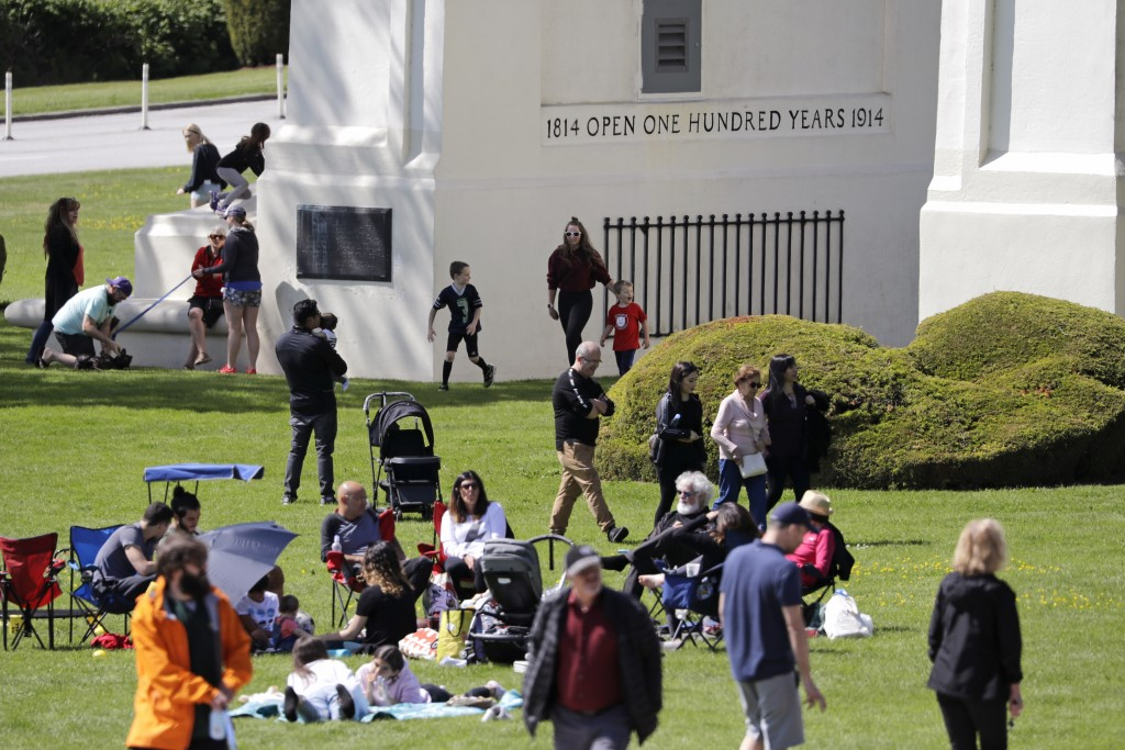 In this photo taken May 17, 2020, people picnic, play and walk back and forth across the border between the U.S. and Canada in Peace Arch Park in Blai...