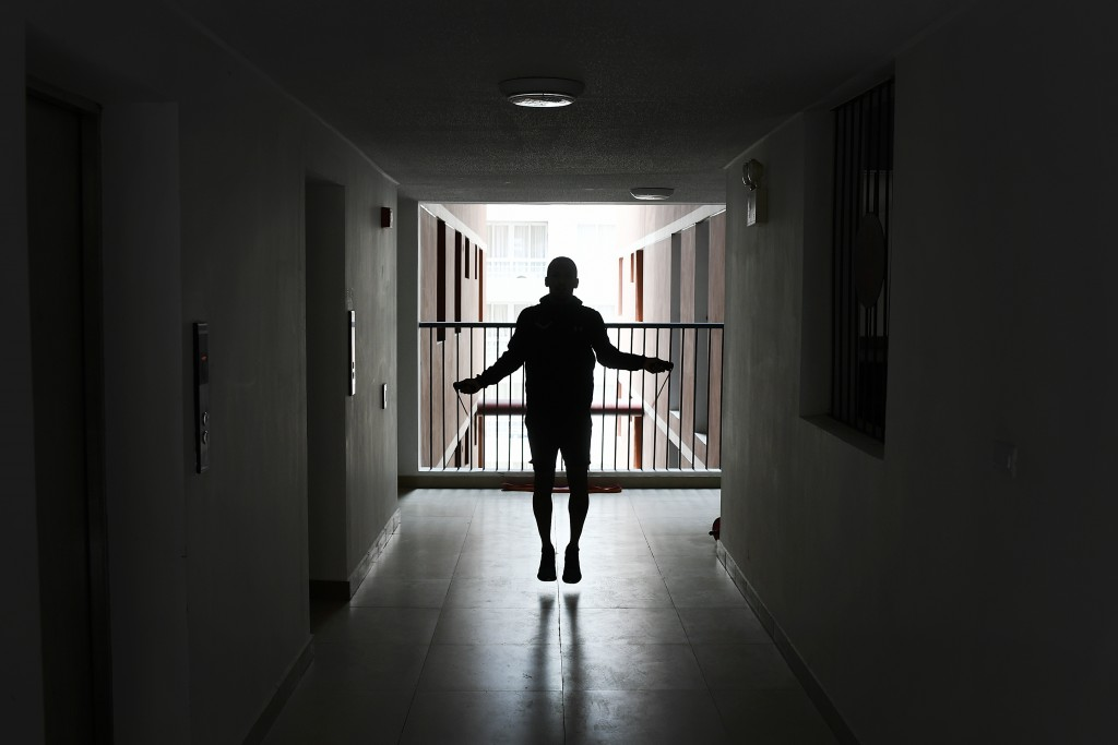 Venezuelan karateka athlete Andres Madera, a gold medalist at the Pan American Games in Peru last year, jumps rope in the hallway of his apartment bui...