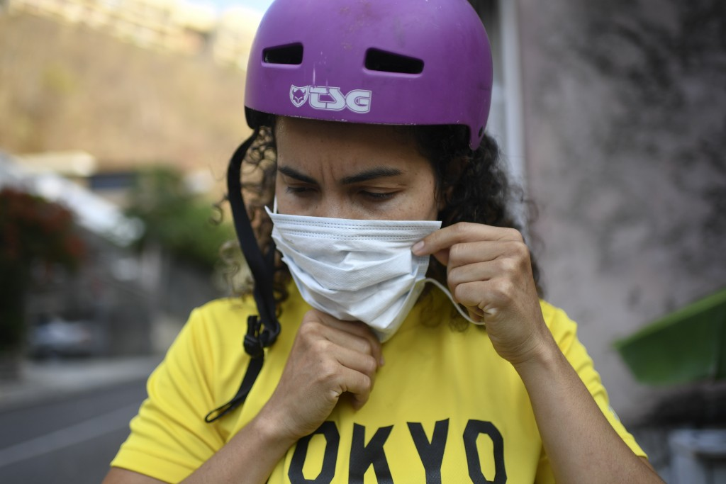 Venezuelan Olympic medalist Stefany Hernandez, a BMX racing cyclist, puts on a face mask amid the COVID-19 pandemic before training in Caracas, Venezu...