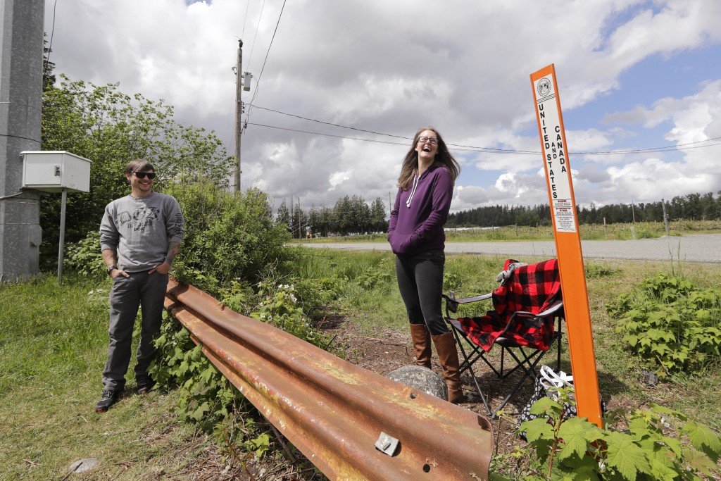 In this photo taken May 17, 2020, Kris Browning, right, laughs as she stands in Canada while visiting her husband, Tim Browning, in the U.S., near Lyn...