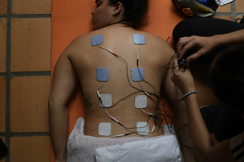 Venezuelan Olympic medalist Stefany Hernandez, a BMX racing cyclist, receives electro-stimulation pads on her back during a muscle relaxation session ...