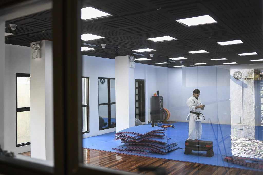 Venezuelan karateka athlete Antonio Diaz, a two-time world champion, checks his cell phone in his dojo, where he also taught before the lockdown, in C...