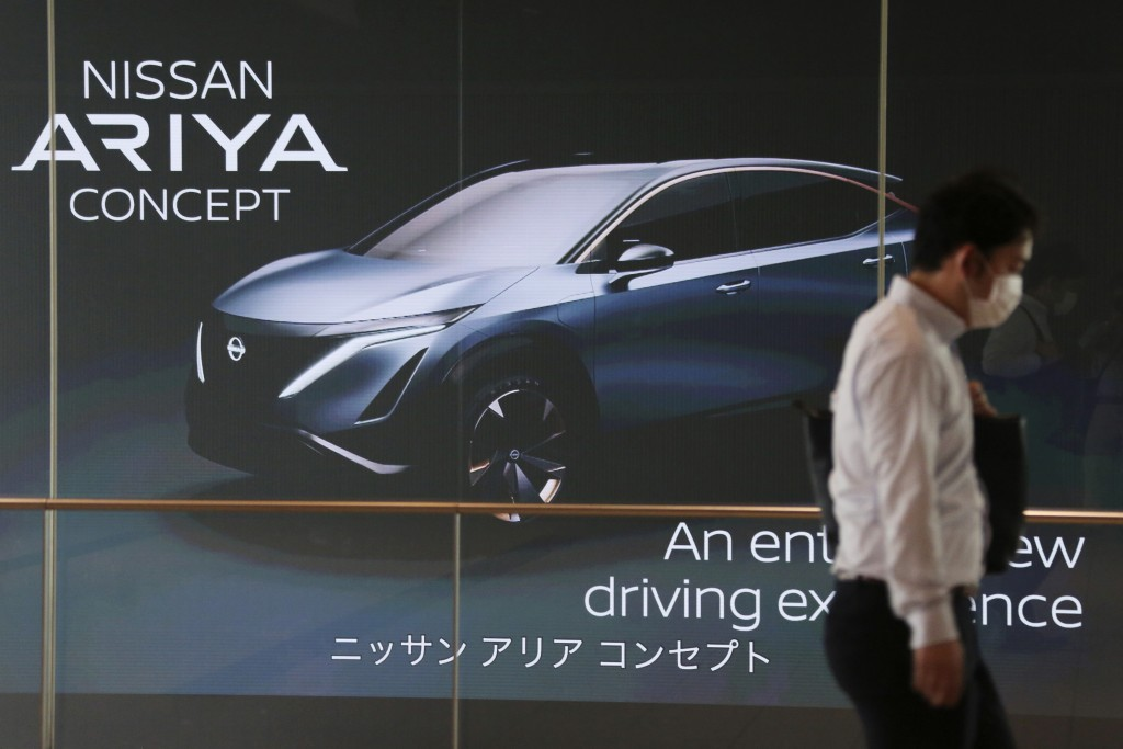 A man walks past the global headquarters of Nissan Motor Co., Ltd. in Yokohama near Tokyo, Wednesday, May 27, 2020. The Japanese-French auto alliance ...