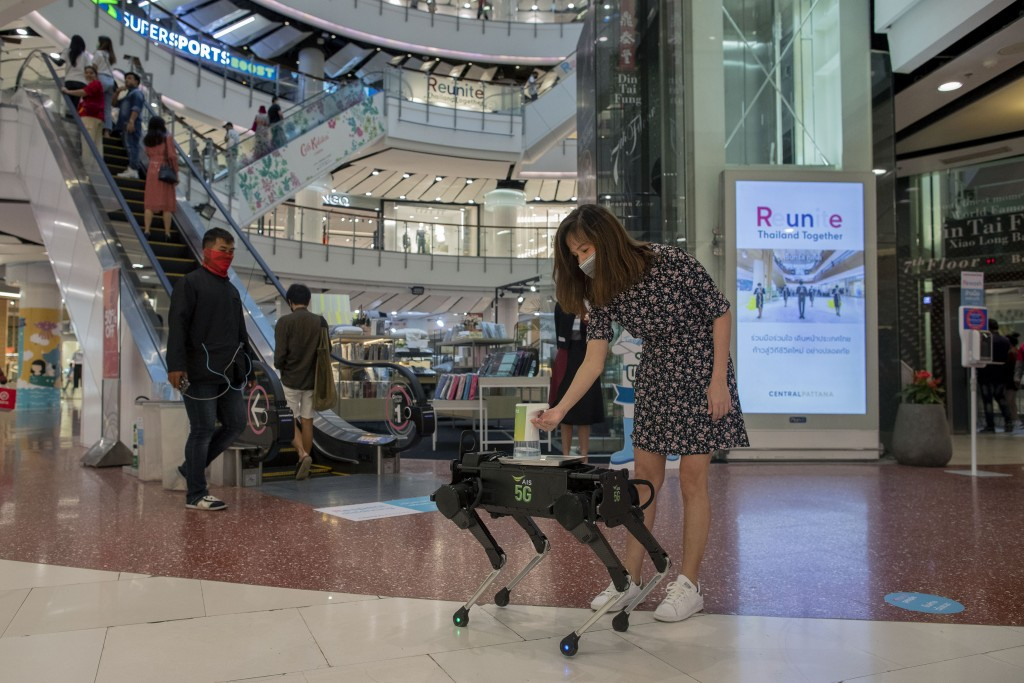 A woman disinfects her hands from a mobile robot that carries a container of sanitization liquid at Central World, an upmarket shopping mall in Bangko...