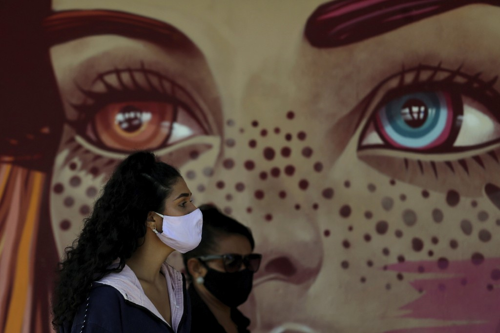 Women wear face masks amid the new coronavirus pandemic as they wait for a quick test at a COVID-19 testing site set up on a public school's basketbal...
