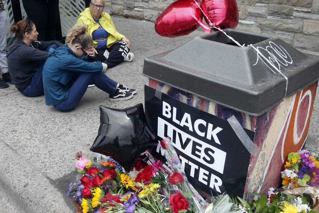 Mourners gather near the site of the death of a man, Tuesday, May 26, 2020, who died in police custody Monday night in Minneapolis after video shared ...