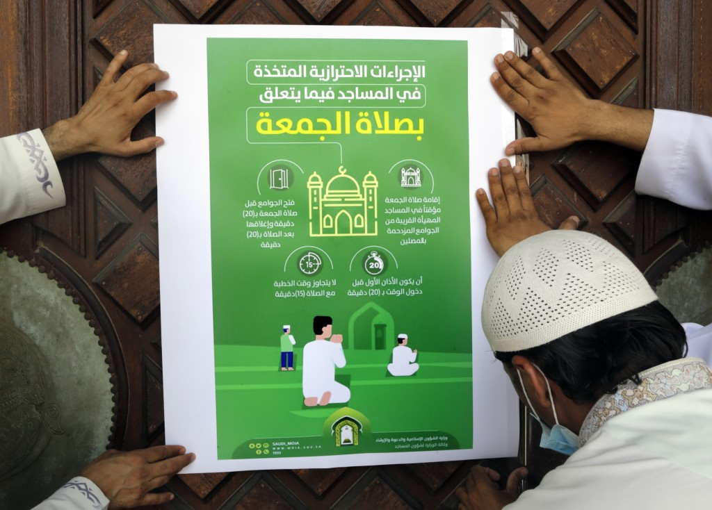 """Workers place a poster with Arabic reads, """"the precautionary measures and instructions inside mosques for Friday prayers"""" at al-Mirabi Mosque in Jidda..."""