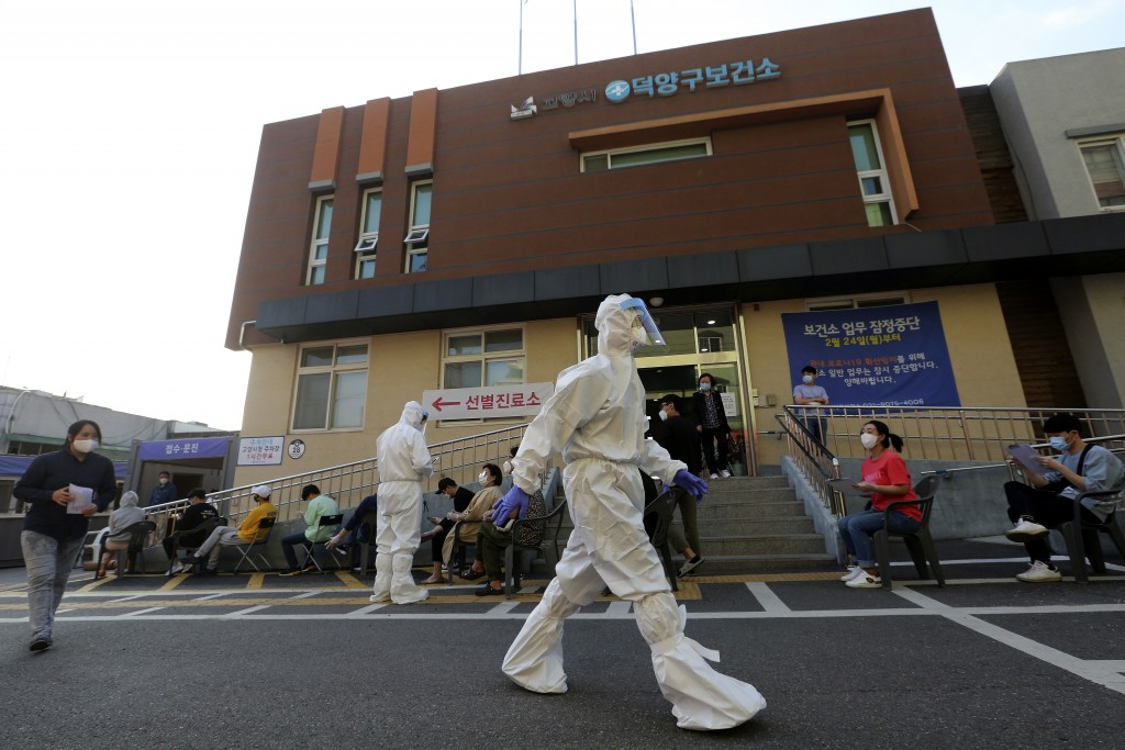 A health official wearing protective gear passes by people sitting and waiting for test for the new coronavirus at a public health center in Goyang, S...