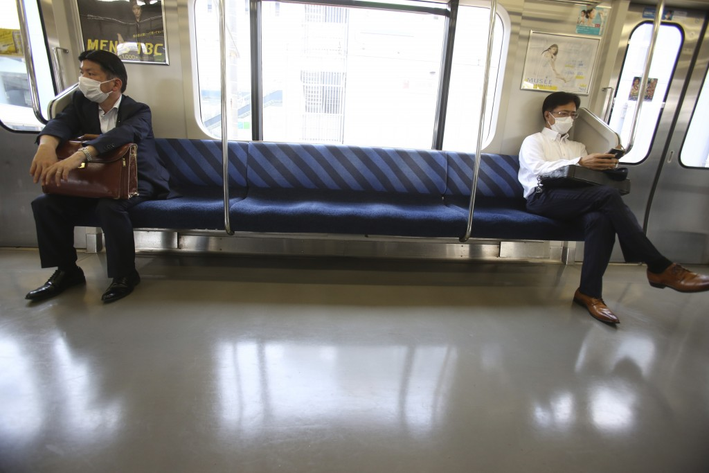 People wearing face masks to protect against the spread of the new coronavirus keep social distancing in a train in Yokohama, near Tokyo, Thursday May...