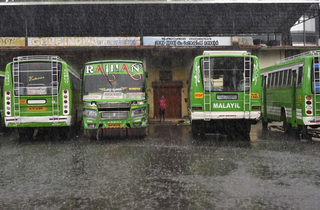 A man wearing a mask stands next to buses that have not been plying for near past two months as it rains in Kochi, Kerala state, India, Thursday, May ...