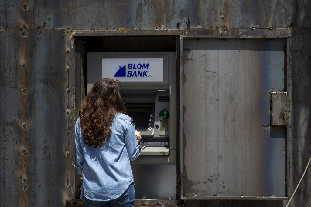 In this Wednesday, May 13, 2020 photo, a woman uses an ATM machine that can be covered by iron shields to prevent acts of sabotage by protesters, in B...