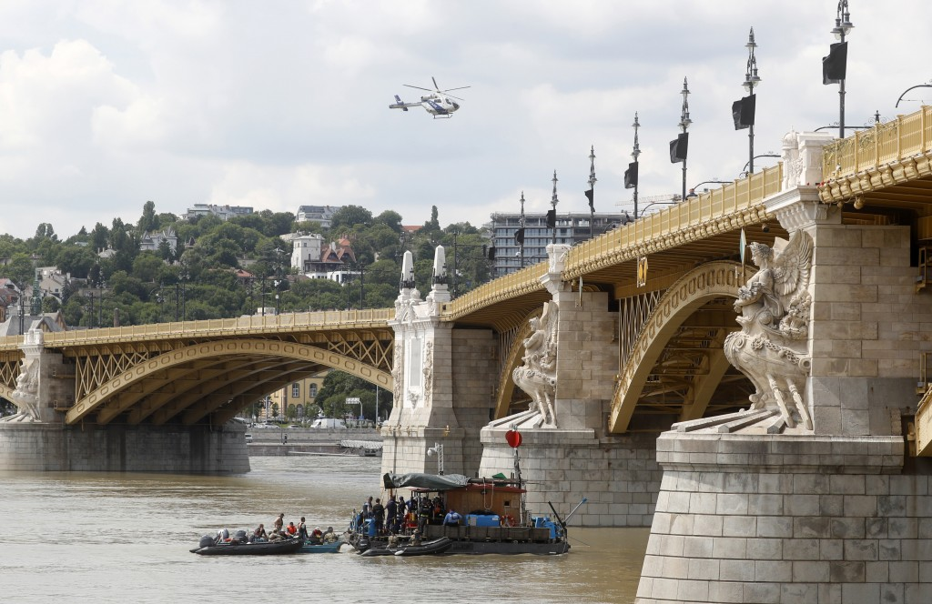 FILE - In this Tuesday, June 4, 2019 a police helicopter flies over the Margit bridge over the Danube river where a sightseeing boat capsized in Budap...