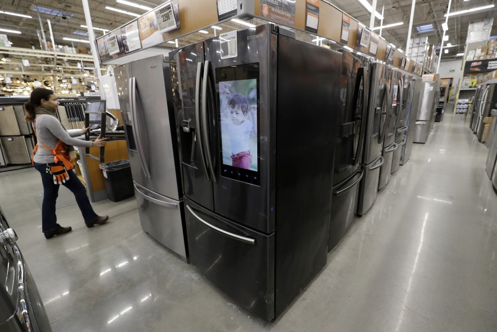 FILE - In this Jan. 27, 2020 file photo a worker pushes a cart past refrigerators at a Home Depot store location in Boston. On Thursday, May 28, the C...
