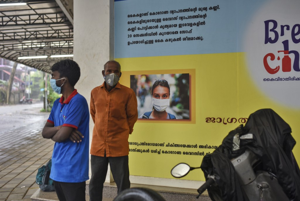 Indians wearing masks stand next to a signage that urges people to wash their hands and wear masks to protect against the COVID-19 pandemic in Kochi, ...