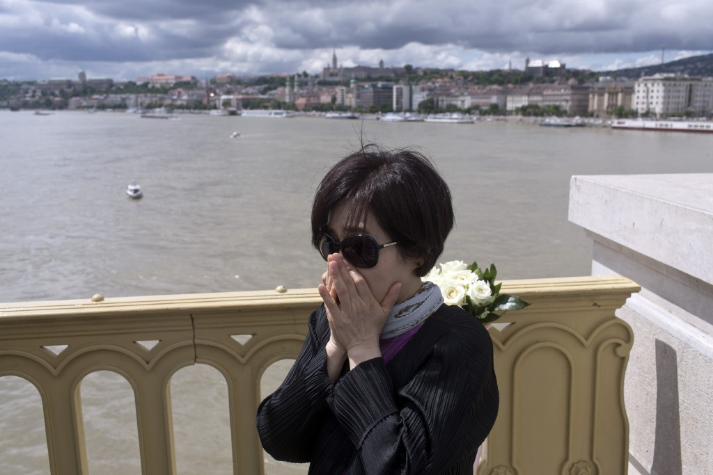 FILE - In this Friday, May 31, 2019 file photo a tourist from South Korea gestures as she stands on the Margit bridge over the Danube river where a si...