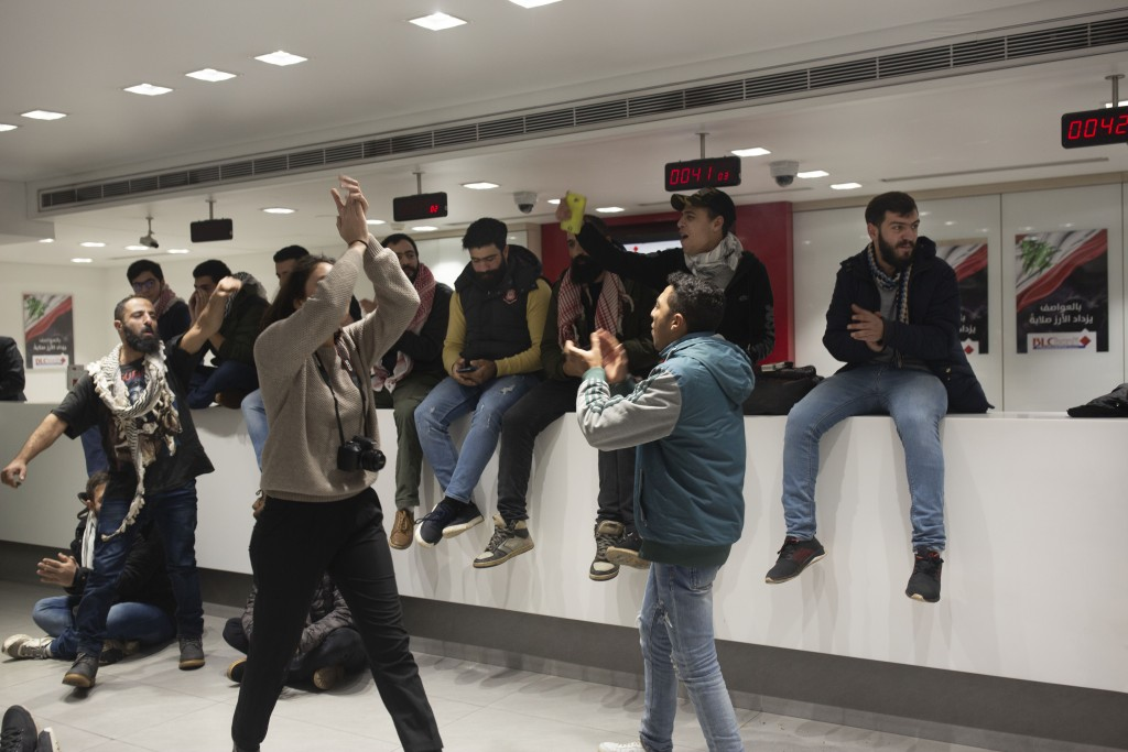 FILE - In this Dec. 28, 2019 file photo, anti-government protesters occupy the Hamra branch of BLC Bank, in Beirut, Lebanon. Riad Salameh, Lebanon's l...