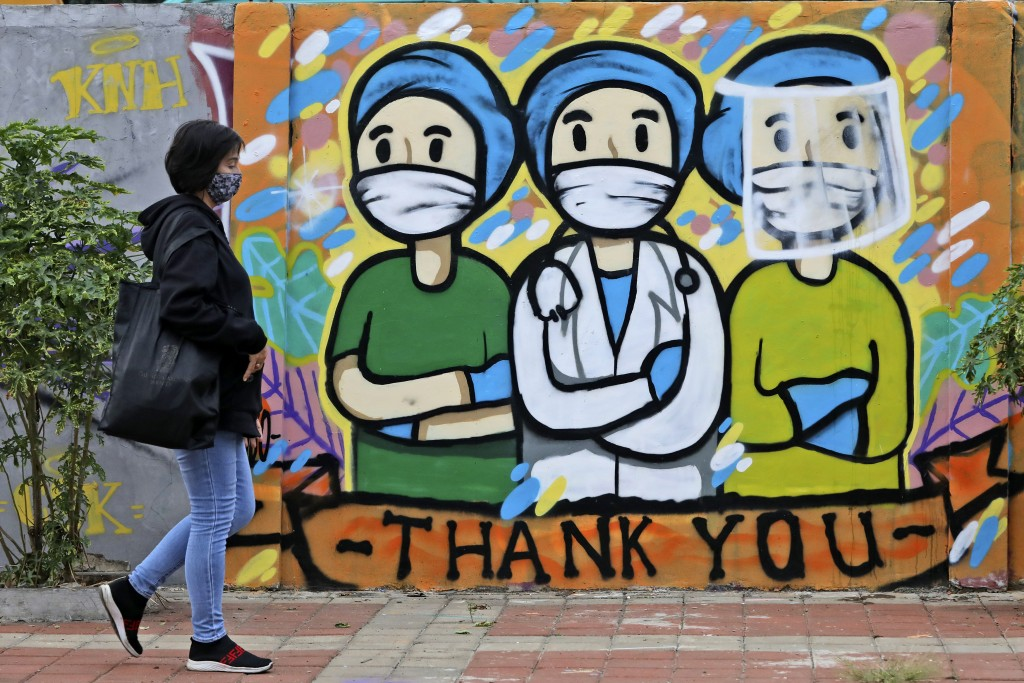 A woman walks past a mural honoring health care workers during the new coronavirus outbreak in Jakarta, Indonesia, Thursday, May 28, 2020. (AP Photo/D...