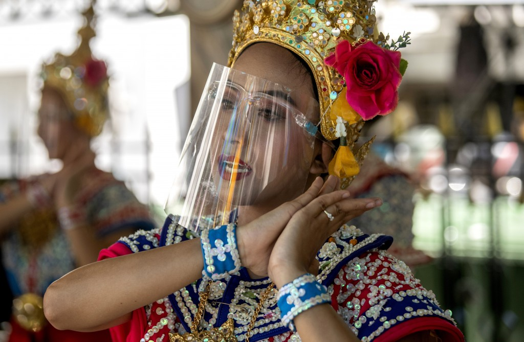A Thai classical dancer wearing face shield to help curb the spread of the coronavirus performs at the Erawan Shrine in Bangkok, Thailand, Thursday, M...