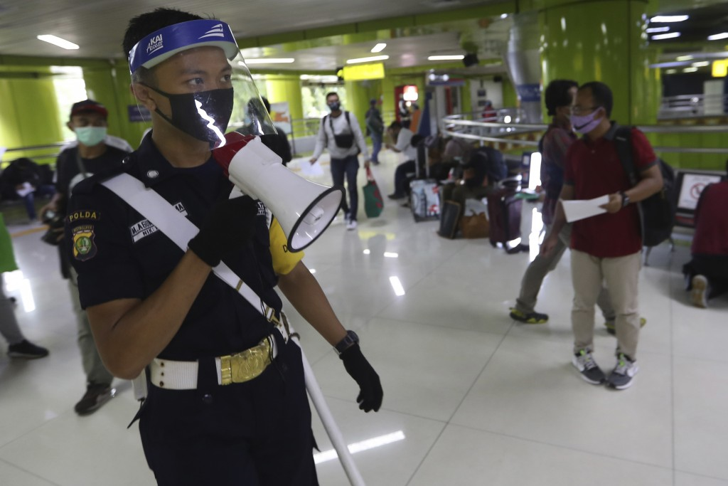 A security guard wearing protective gears uses a megaphone to give directions to arriving train passengers to have their travel documents checked at G...