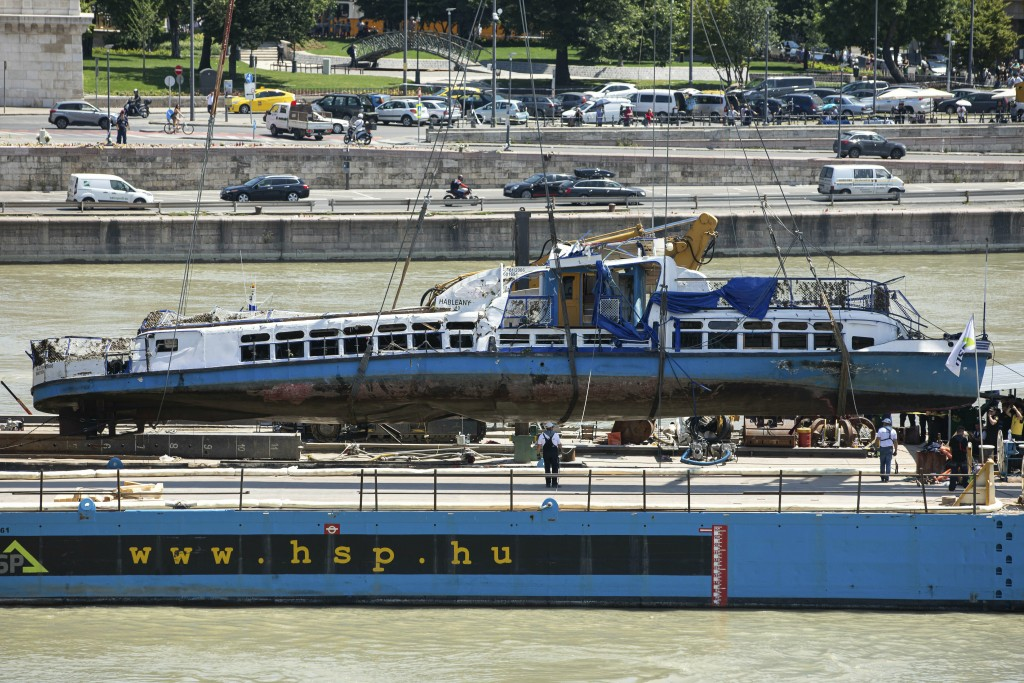 FILE- In this Tuesday, June 11, 2019, file photo a crane places the wreckage of the sightseeing boat on a transporting barge at Margaret Bridge, the s...