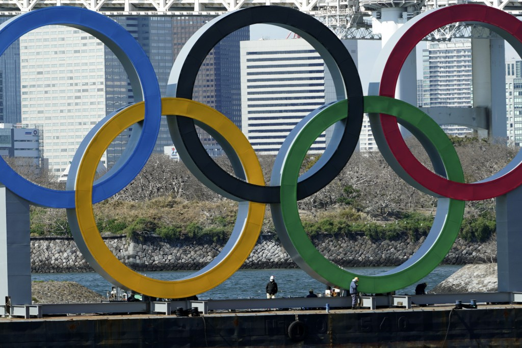 FILE - In this March 24, 2020, file photo, workers stand at the bottom of the Olympic rings at Tokyo's Odaiba district. Just two months after the unpr...