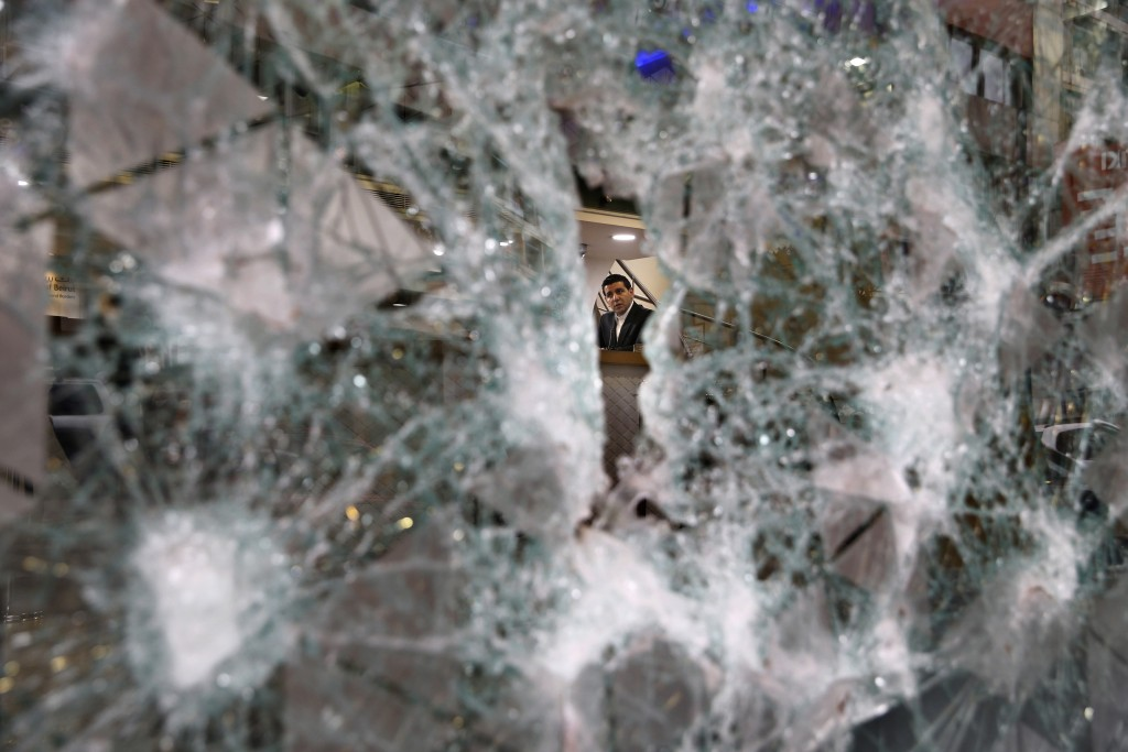 FILE - In this Jan. 15, 2020 file photo, a bank employee is seen through the broken facade of a branch of the Bank of Beirut that was smashed by anti-...