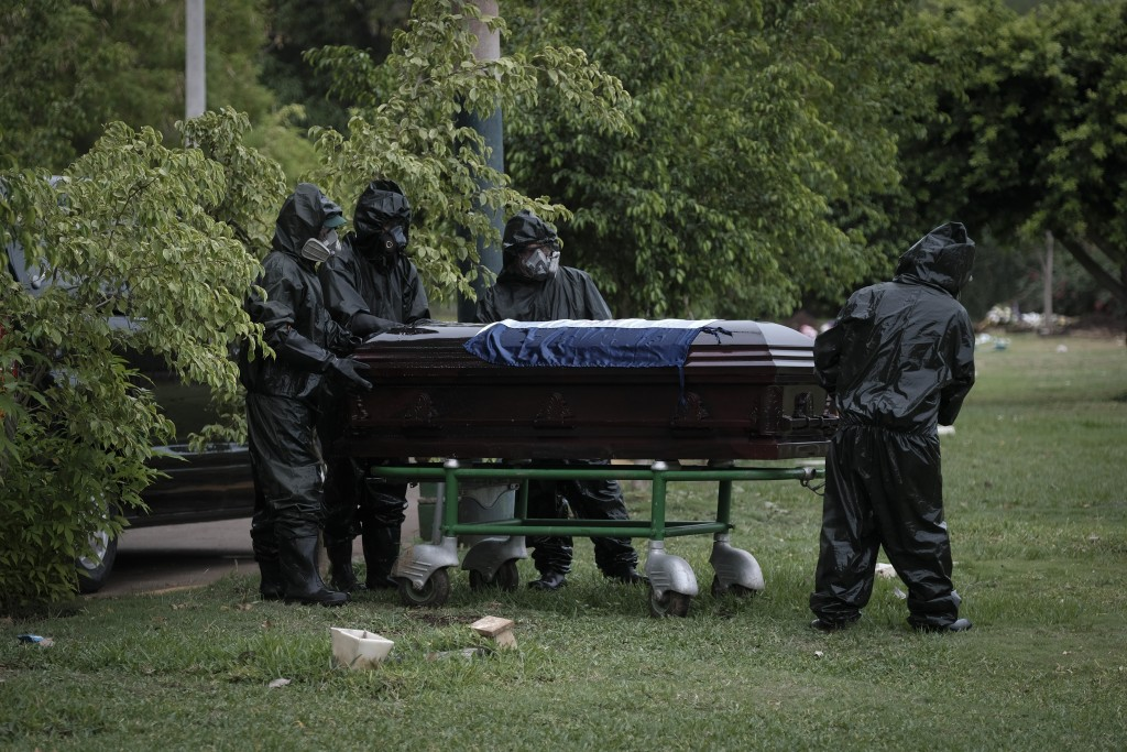 Workers in full protection gear against the spread of the new coronavirus move the coffin with the body of journalist Carlos Bermudez for burial at th...
