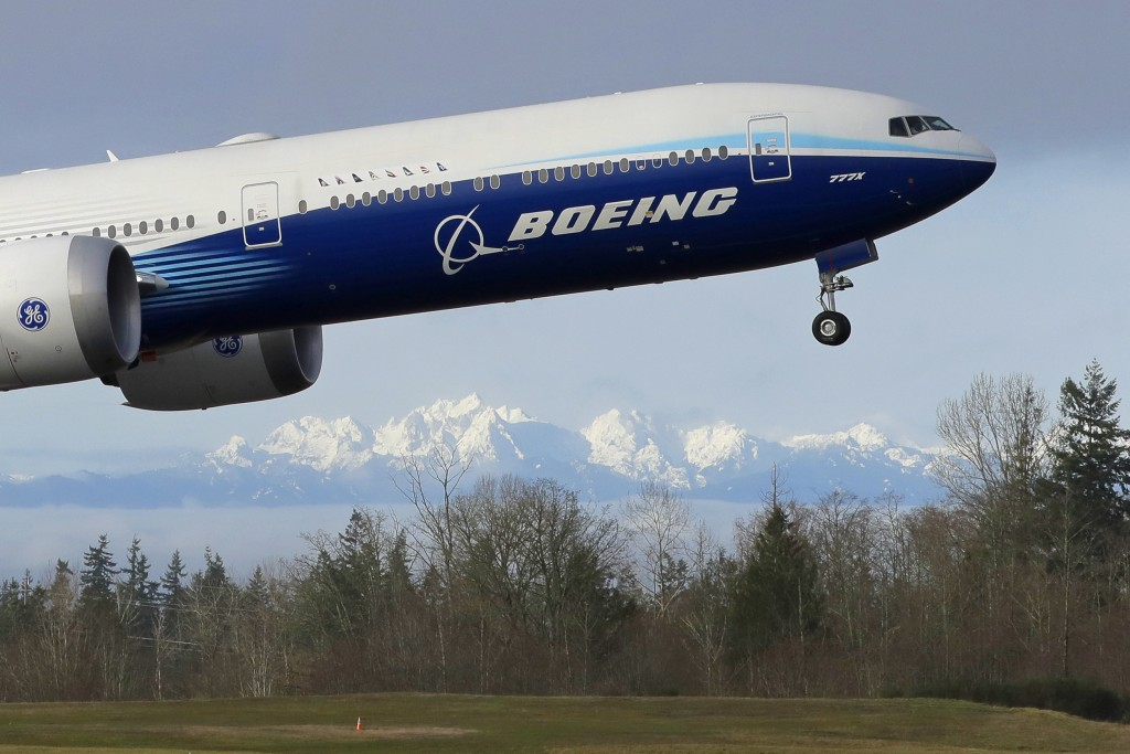 FILE - In this Jan. 25, 2020, file photo a Boeing 777X airplane takes off on its first flight with the Olympic Mountains in the background at Paine Fi...