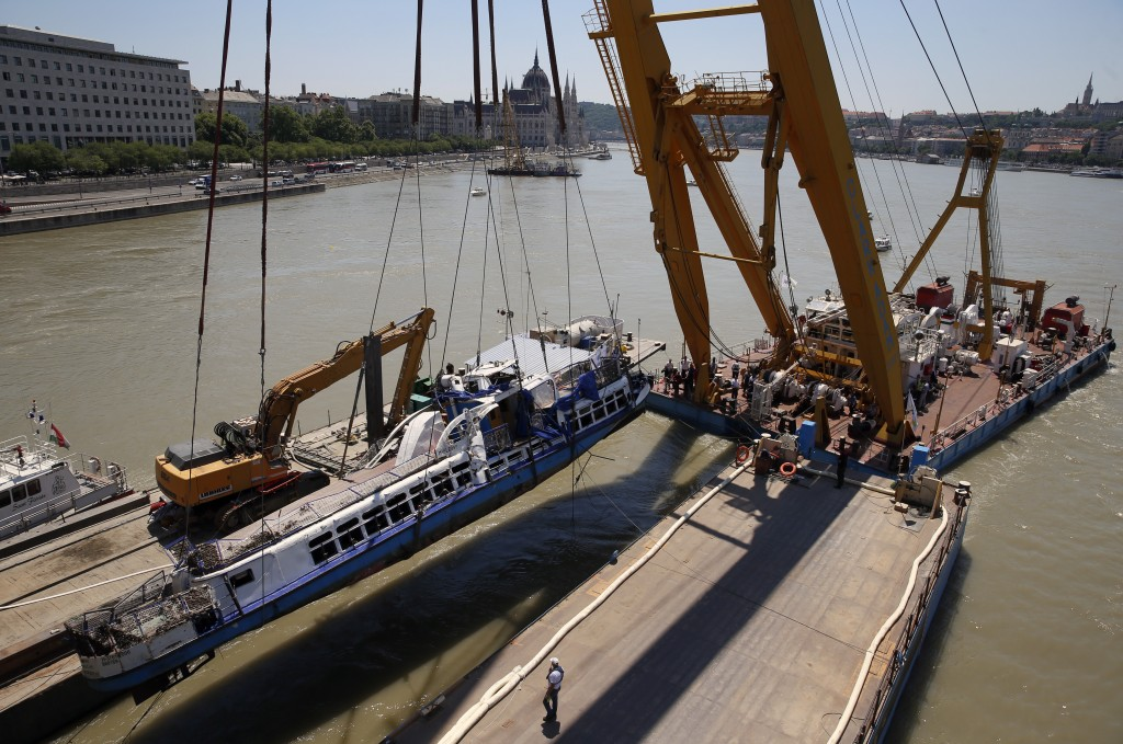 FILE - In this Tuesday, June 11, 2019, file photo, a crane lifts the sightseeing boat out of the Danube river in Budapest, Hungary. Preparations are u...