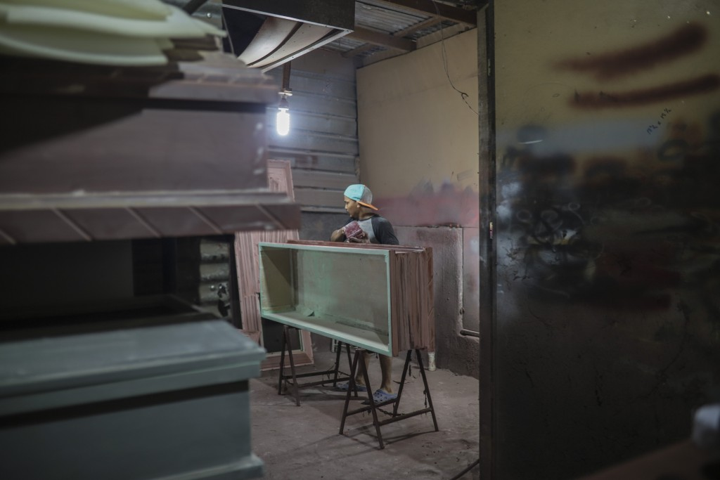A man builds coffins at the La Amistad funeral home in Managua, Nicaragua, Wednesday, May 27, 2020. President Daniel Ortega's government has stood out...