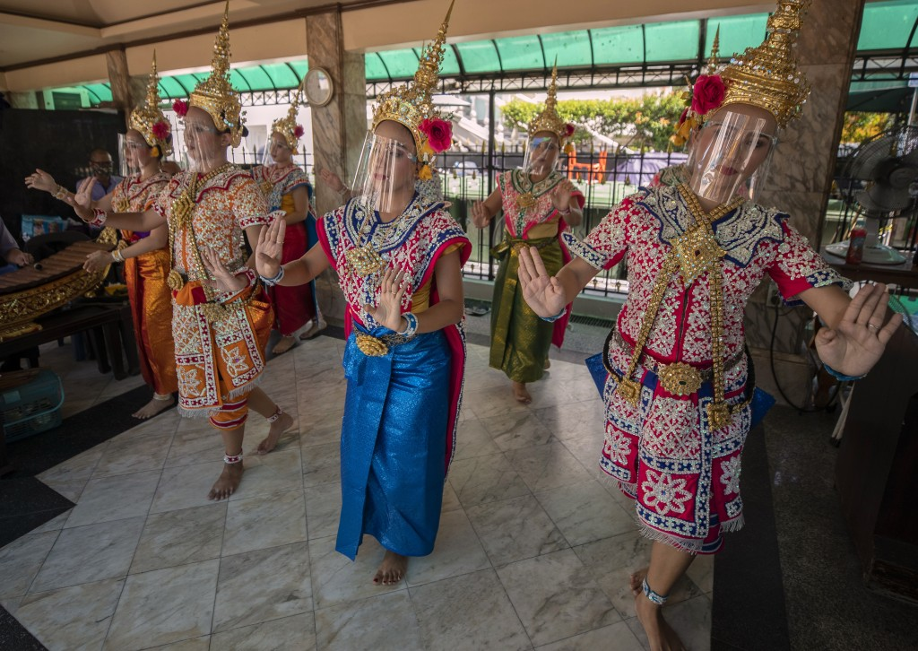 Thai classical dancers wearing face shield to help curb the spread of the coronavirus perform at the Erawan Shrine in Bangkok, Thailand, Thursday, May...