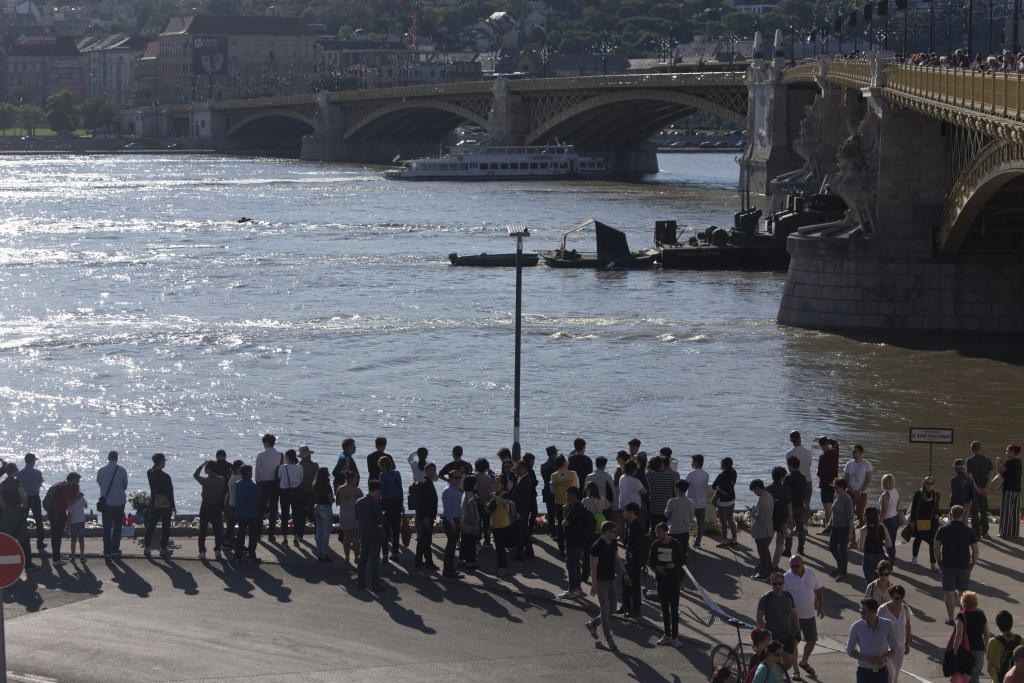 FILE - In this Saturday, June 1, 2019 file photo, family and friends of victims gather near flower tributes on the banks of the Danube river where a s...