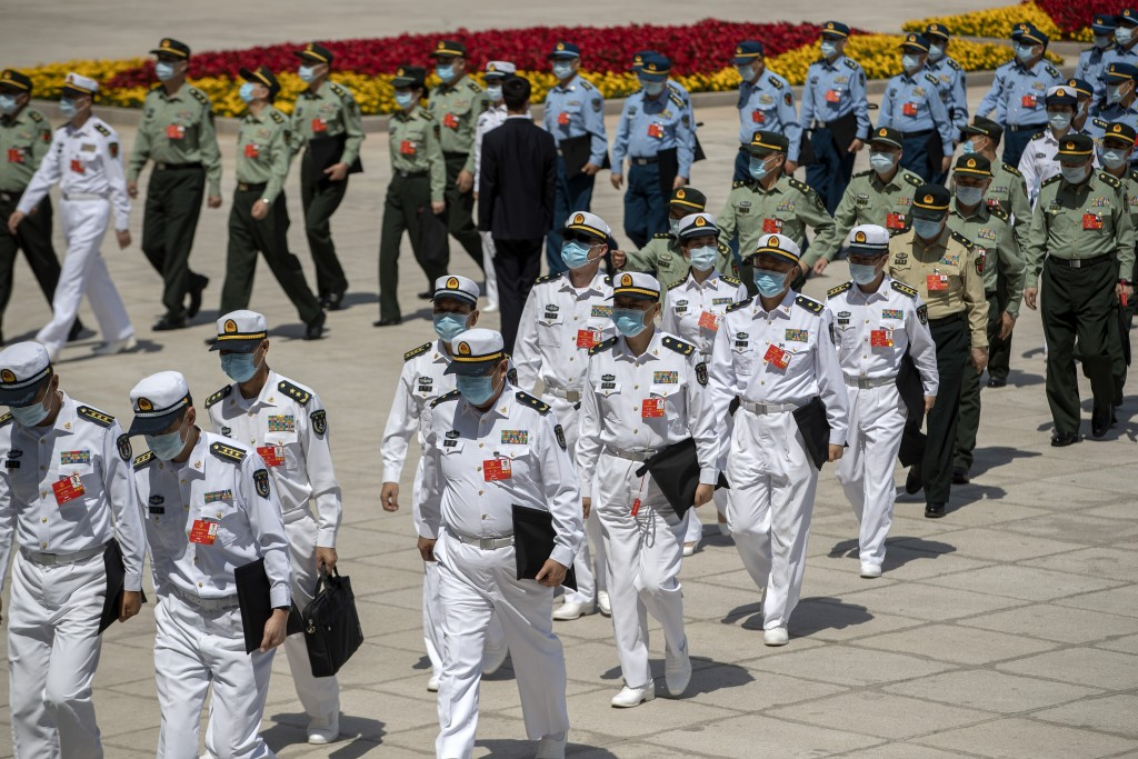Military delegates arrive for the closing session of China's National People's Congress at the Great Hall of the People in Beijing Thursday Ma