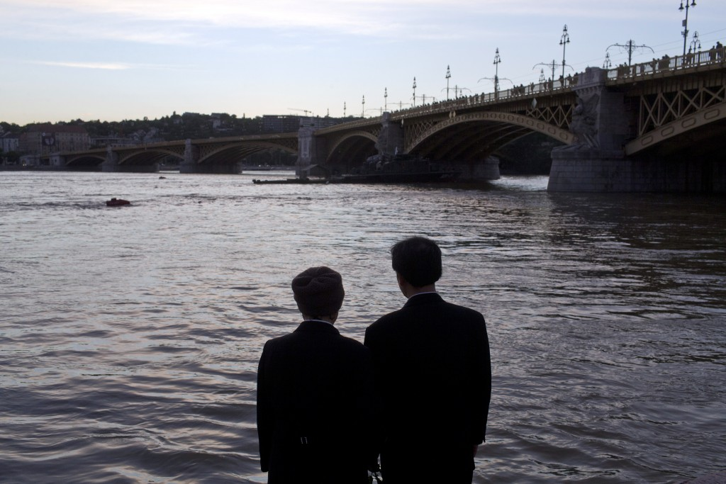 FILE - In this Friday, May 31, 2019 file photo a couple stand on the banks of the Danube river next to Margit bridge where a sightseeing boat had caps...