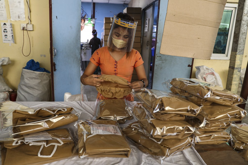 A woman wearing face mask and face shield to help curb the spread of the new coronavirus, checks surgical gown at a packing session at a garment facto...