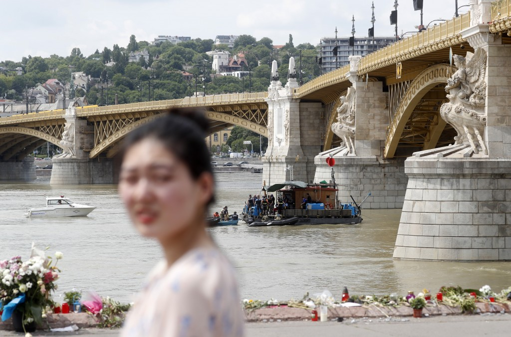 FILE - In this Tuesday, June 4, 2019 a woman walks next to the Margit Bridge on the bank of the Danube River where a sightseeing boat capsized in Buda...