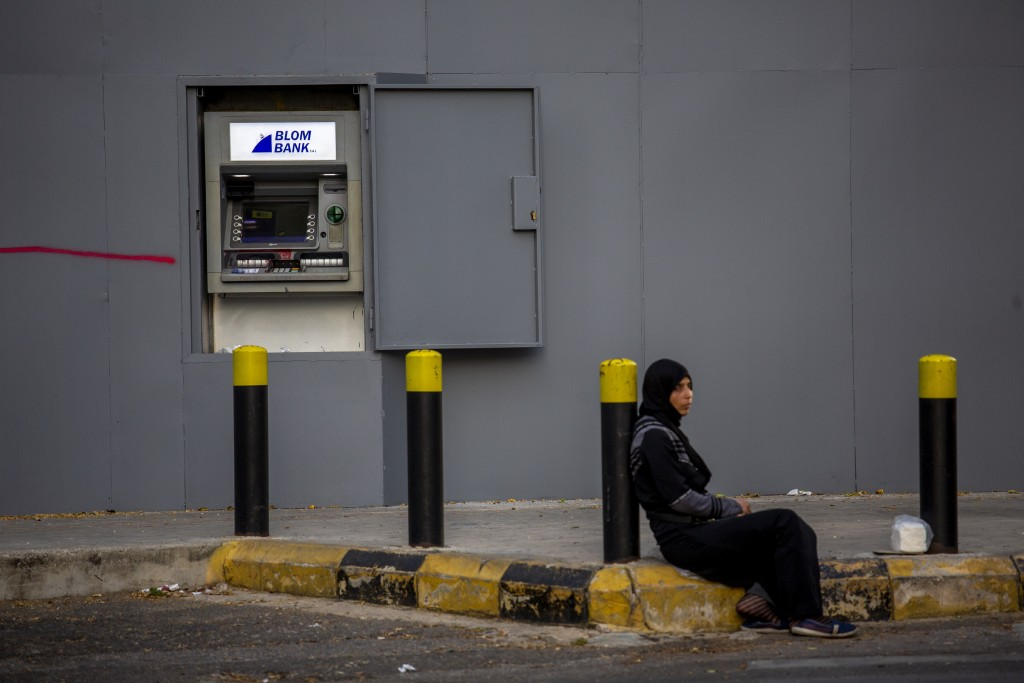 In this Thursday, May 21, 2020 photo, a woman begs on a sidewalk in front an ATM machine covered by iron shields along the facade of a bank to prevent...