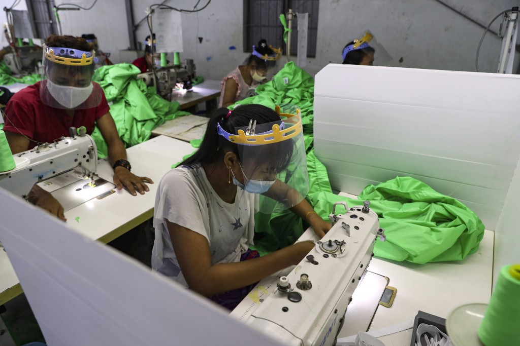 Workers wearing face mask and face shield to help curb the spread of the new coronavirus, sew behind white partition surrounding their sewing tables a...