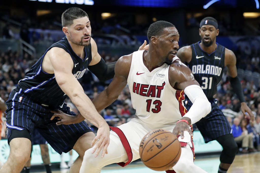 FILE - In this Feb. 1, 2020, file photo, Miami Heat forward Bam Adebayo (13) tries to get around Orlando Magic center Nikola Vucevic, left, and guard ...
