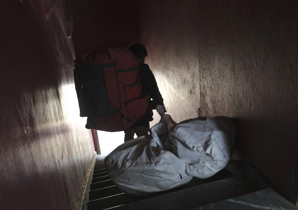 An Amazon delivery person drags a bag containing packages as he steps out from his office to make deliveries in Kohima capital of the northeastern I