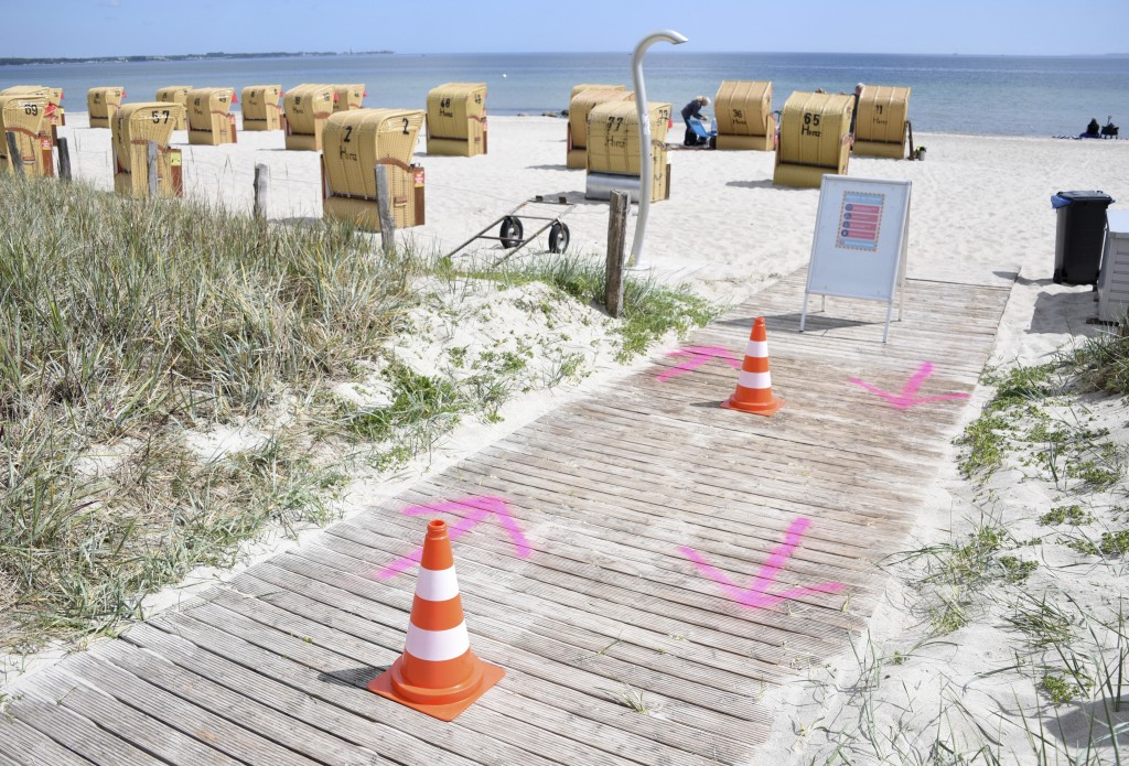 In this Wednesday, May 20, 2020 photo, pylons and arrows sprayed on the ground, regulate the access to the beach at the Baltic Sea in Haffkrug, German...