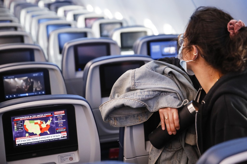 A passenger wears personal protective equipment on a Delta Airlines flight as a map depicting the spread of COVID-19 is displayed on a monitor after l...