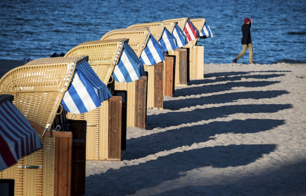 In this Thursday, May 21, 2020 photo, beach chairs cast long shadows on the beach at the Baltic Sea Luebeck-Travemuende, Germany. Germany's states, wh...